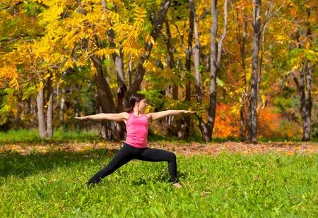 virabhadrasana: Woman exercises in the autumn forest yoga virabhadrasana pose