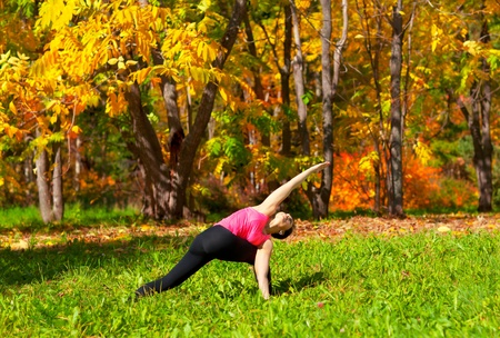 Woman exercises in the autumn forest yoga parivrita parshvakonasana pose photo