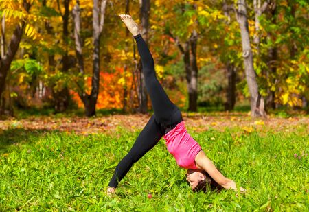 Woman exercises in the autumn forest yoga Adho mukha eka pada shvanasana pose photo