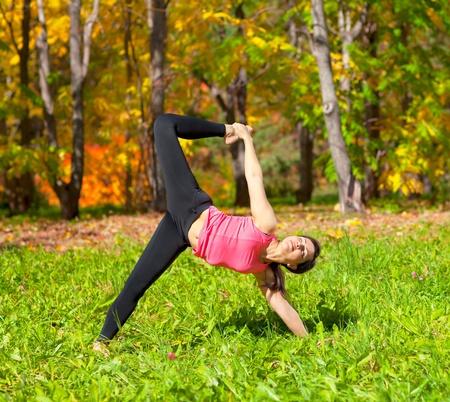 ardha: Woman exercises in the autumn forest yoga Ardha Chandra chapasana pose Stock Photo