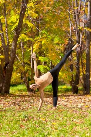 chandrasana: Man exercises in the autumn forest yoga Ardha chandrasana pose