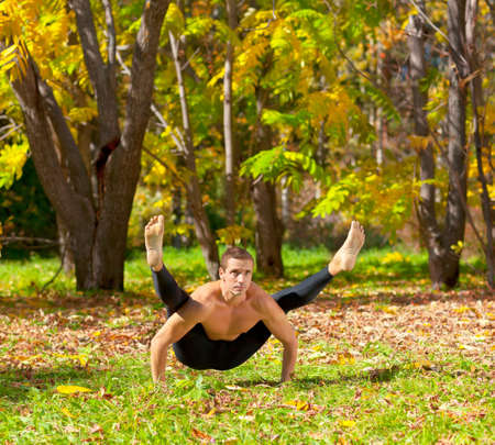 Man exercises in the autumn forest yoga tittibhasana pose photo
