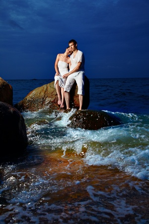 outdoor portrait of young romantic couple in white cotton clothes sitting on stone with waves around at night beach of Phuket island, Thailand photo