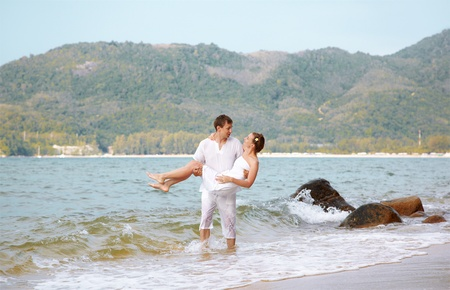 outdoor portrait of young romantic couple in white cotton clothes on beach of Phuket island, Thailand. guy is holding girl on hands photo