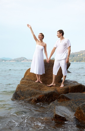 outdoor portrait of young romantic couple standing on stone and waving hands among azure waters of Phuket island, Thailand  photo