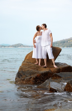 outdoor portrait of young romantic couple kissing on stone among azure waters of Phuket island, Thailand photo