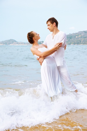 outdoor portrait of young romantic couple in white cotton clothes embracing each other on beach of Phuket island, Thailand photo