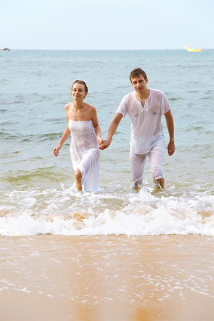 outdoor portrait of young romantic couple in white cotton clothes on beach of Phuket island, Thailand photo