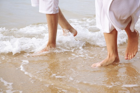 a newly married couple: body part outdoor portrait of couples legs in white cotton clothes walking along coastal strip of Phuket island, Thailand