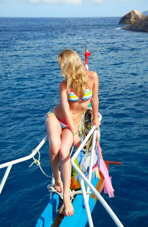 outdoor portrait of beautiful young blonde woman in bikini on yachts prow photo