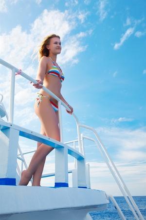 outdoor portrait of beautiful young blonde woman in bikini on yacht photo