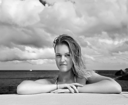 outdoor portrait of beautiful young blonde woman outdoors. azure sea and cloudy sky on background photo