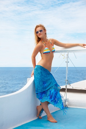 pareo: outdoor portrait of beautiful young blonde woman in bikini and sunglasses and pareo on yacht