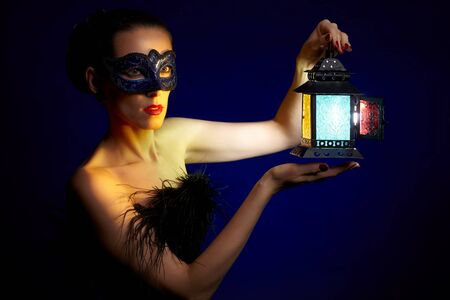 portrait of beautiful brunette woman in carnival mask with shining lantern in hands photo