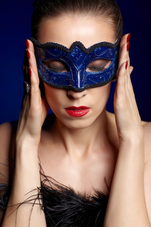 portrait of beautiful brunette woman in carnival mask touching temples like she has headache photo