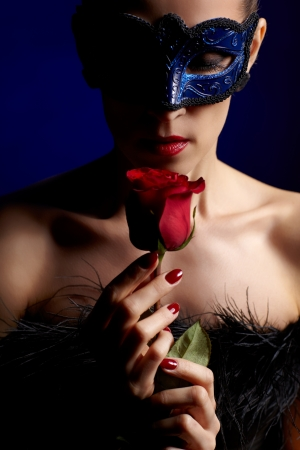 portrait of beautiful brunette woman in carnival mask smelling red roses aroma with eyes closed photo
