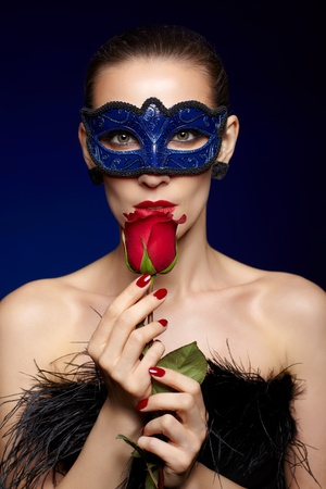 portrait of beautiful brunette woman in carnival mask touching her lips with red rose photo