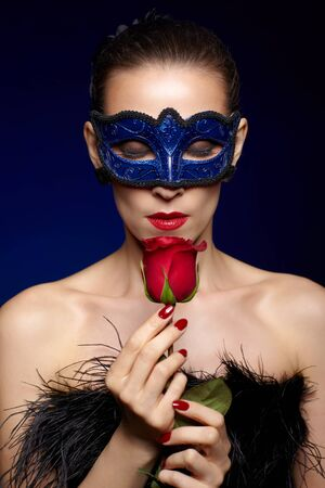 portrait of beautiful brunette woman in carnival mask with red rose with eyes closed photo