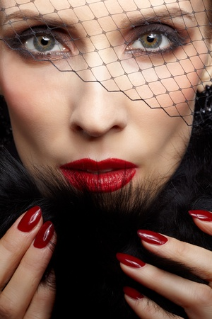 close-up portrait of beautiful brunette woman in veil touching black fur coat with manicured fingers photo