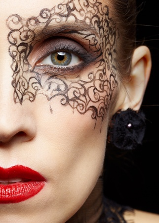 close-up half-face portrait of beautiful woman with facial bodyart photo