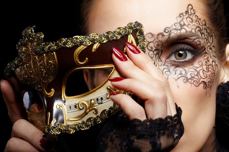 close-up portrait of beautiful brunette woman with facial body art hiding half of her face with carnival venetian mask photo