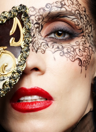 close-up portrait of beautiful brunette woman with facial body art hiding half of her face with carnival mask photo