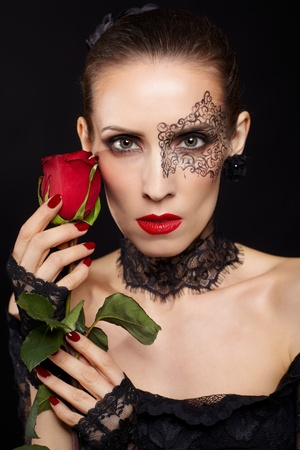 portrait of beautiful brunette woman with facial bodyart in black lacy dress and gloves with red rose flower in hand photo