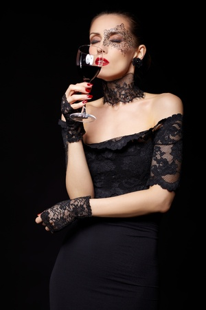 portrait of beautiful brunette woman sommelier in lacy black dress and gloves with face body art holding glass of red wine in hand with eyes shut photo