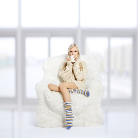 portrait of beautiful blonde sitting with cup on big white furry arm-chair Stock Photo - 12105958