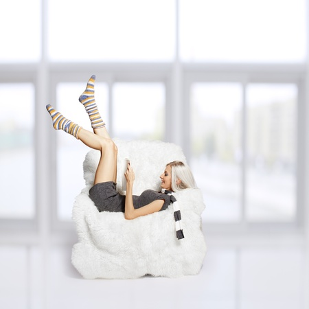 portrait of beautiful blonde laying with book in big white furry arm-chair photo