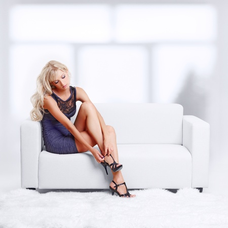 full-length portrait of beautiful young blond woman on couch checking court shoe fastener photo