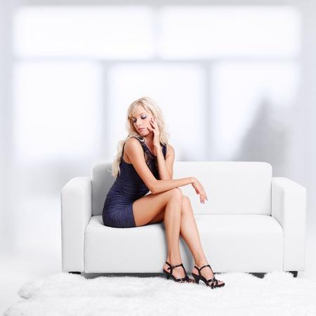mujer sentada: retrato de cuerpo entero de la hermosa joven rubia en el sofá con pieles blancas en el suelo