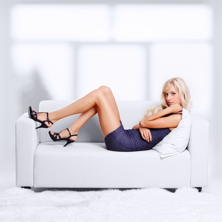 full-length portrait of beautiful young blond woman on couch with white furs on floor Stock Photo - 12105985