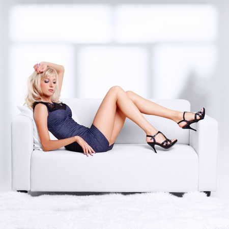 large woman: full-length portrait of beautiful young blond woman on couch with white furs on floor