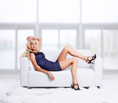 attractive couch: full-length portrait of beautiful young blond woman on couch with white furs on floor