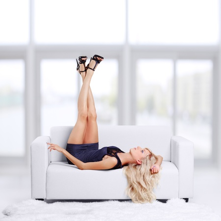 full-length portrait of beautiful young blond woman on couch streching legs in court shoes Stock Photo - 12106130