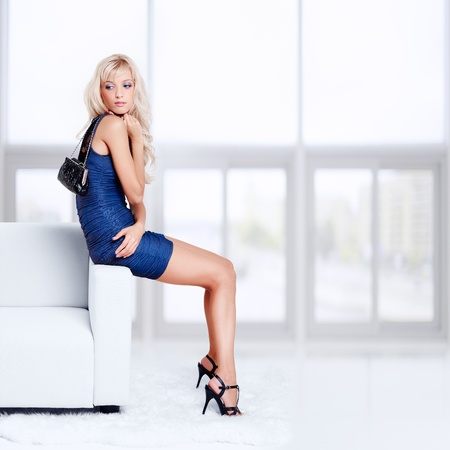 full-length portrait of beautiful young blond woman with handbag sitting on couch with white furs on floor photo