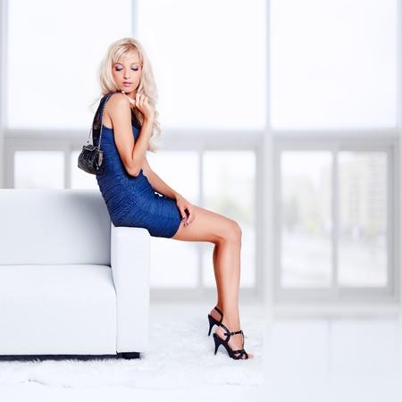 retrato de cuerpo entero de la hermosa joven rubia con el bolso de sentarse en el sofá con pieles blancas en el suelo