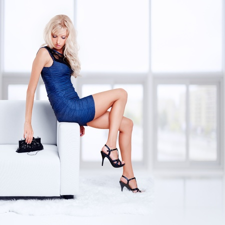 full-length portrait of beautiful young blond woman with handbag sitting on couch with white furs on floor Stock Photo