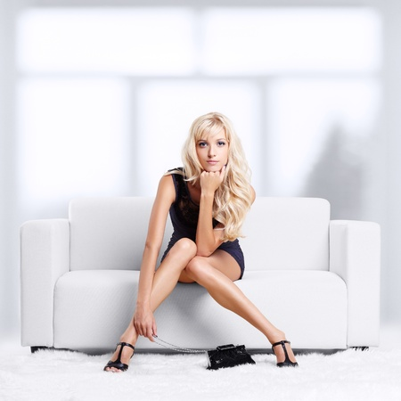 full-length portrait of beautiful young blond woman on couch with white furs on floor Stock Photo - 12106054