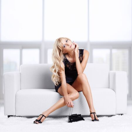 full-length portrait of beautiful young blond woman on couch with white furs on floor Stock Photo - 12106053