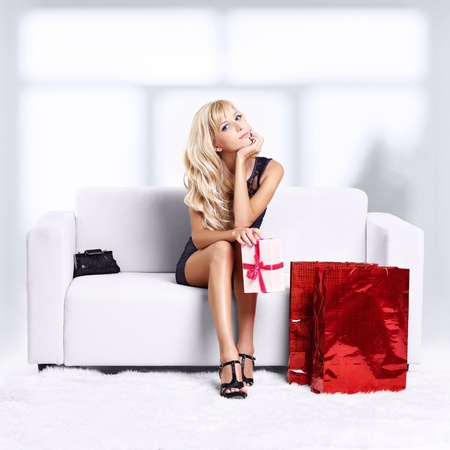 full-length portrait of beautiful young blond woman on couch with shopping bags and gift in hands photo