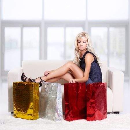 full-length portrait of beautiful young blond woman on couch with shopping bags photo
