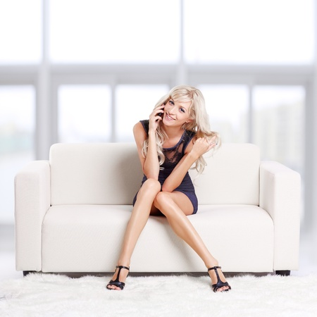 sitting rooms: full-length portrait of beautiful young blond woman on couch speaking over her mobile phone