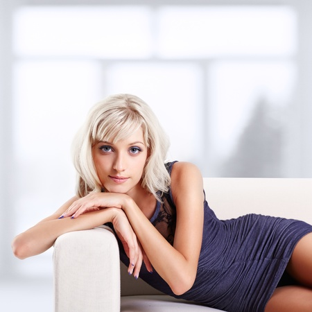 portrait of beautiful young blond woman relaxing on couch  photo