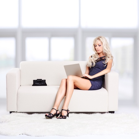 full-length portrait of beautiful young blond woman sitting on couch with laptop on her knees Stock Photo - 12106097