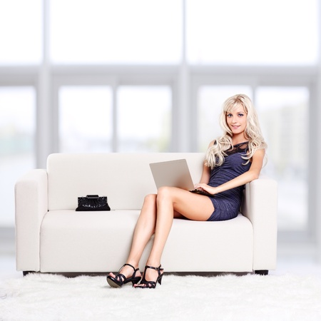 full-length portrait of beautiful young blond woman sitting on couch with laptop on her knees Stock Photo - 12106093