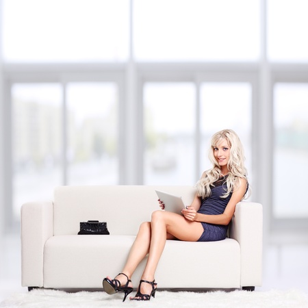 full-length portrait of beautiful young blond woman on couch with tablet pc Stock Photo - 12106133