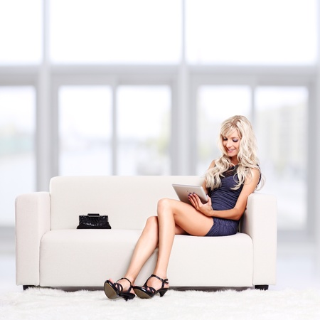 handbag model: full-length portrait of beautiful young blond woman on couch with tablet pc