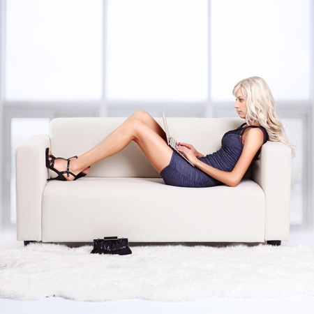 full-length portrait of beautiful young blond woman relaxing on couch with laptop Stock Photo - 12106081